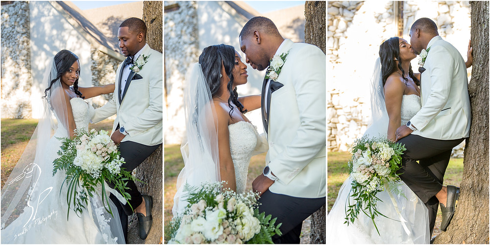 Bradenton Wedding Photographer, The groom leans against a tree as his bride leans in to kiss him in front of United First Methodist Church of Seffner