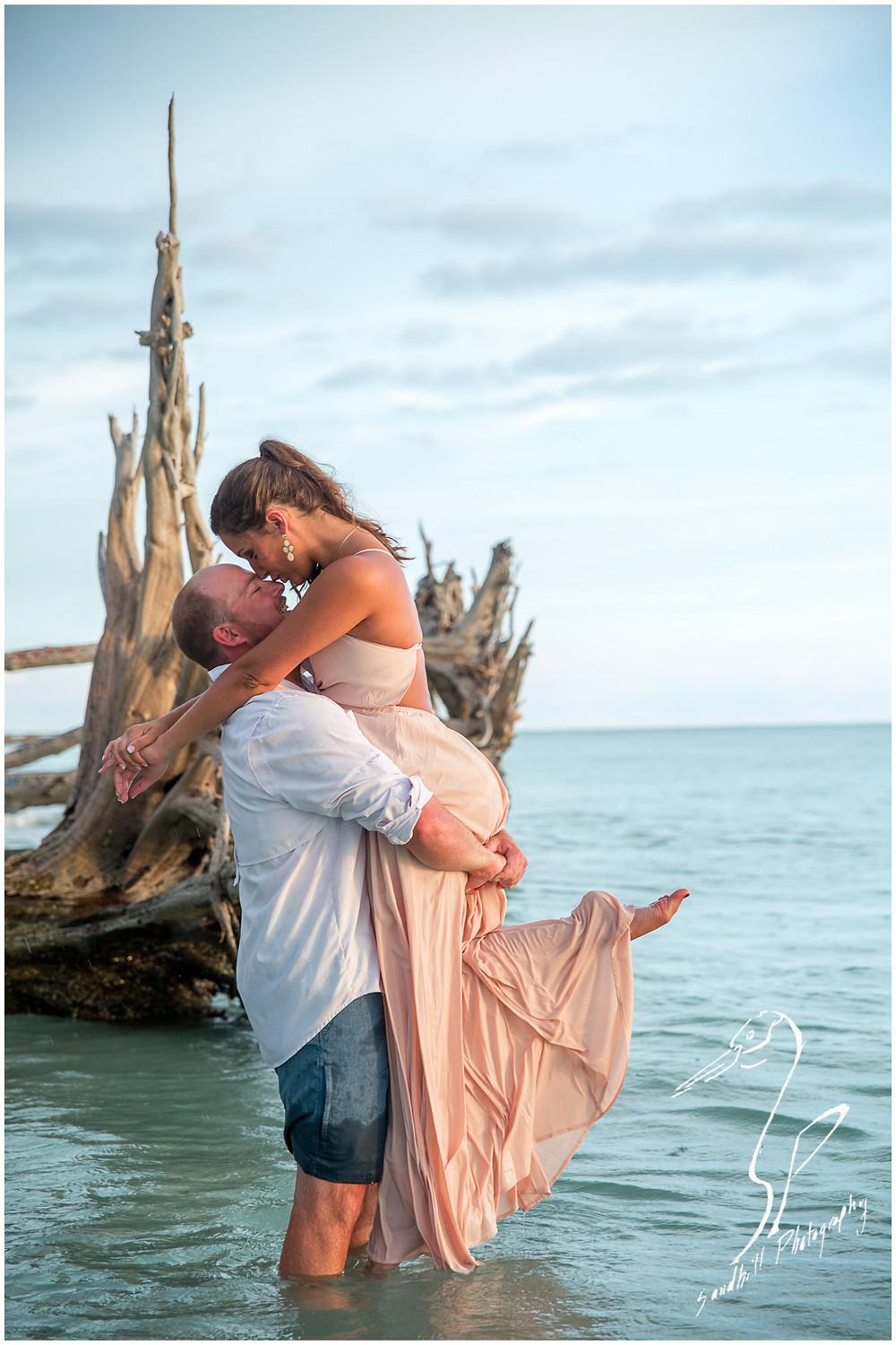 Beer Can Island Engagement Photography, an Engaged man lifts his fiance up out of the water on Longboat Key