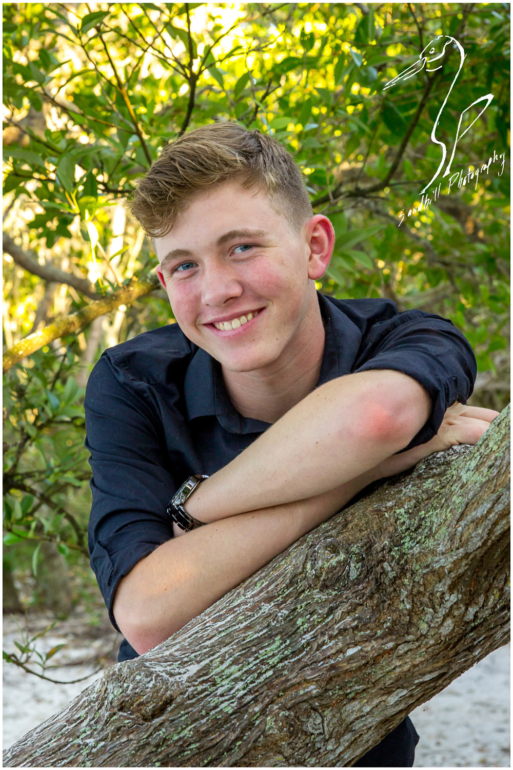 DeSoto National Memorial Photography, Senior Picture of a young man leaning against a tree branch in the woods
