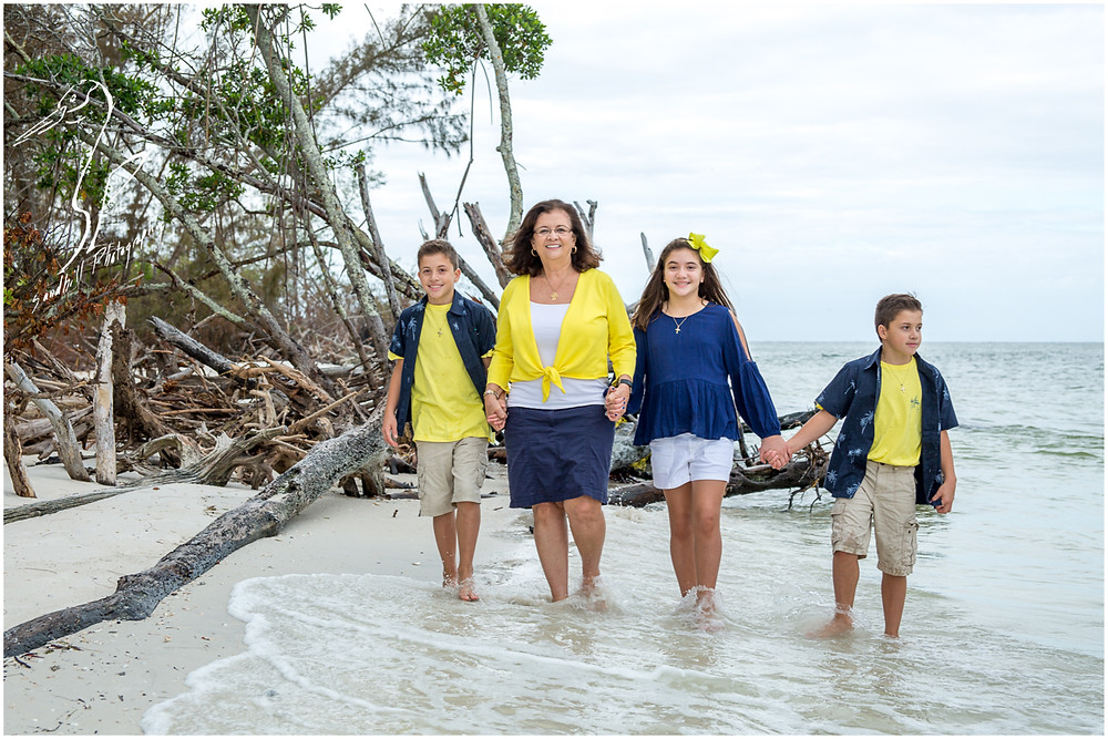 Longboat Key Family Photographer, Grandmother and her grandchildren hold hands and go for a walk on the beach at Beer Can Island