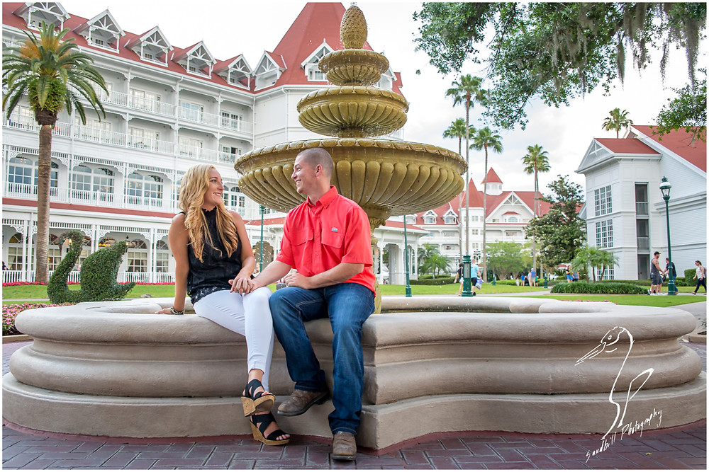 Disney's Grand Floridian Engagement Session, newly engaged couple sit on the edge of the fountain of the resort courtyard