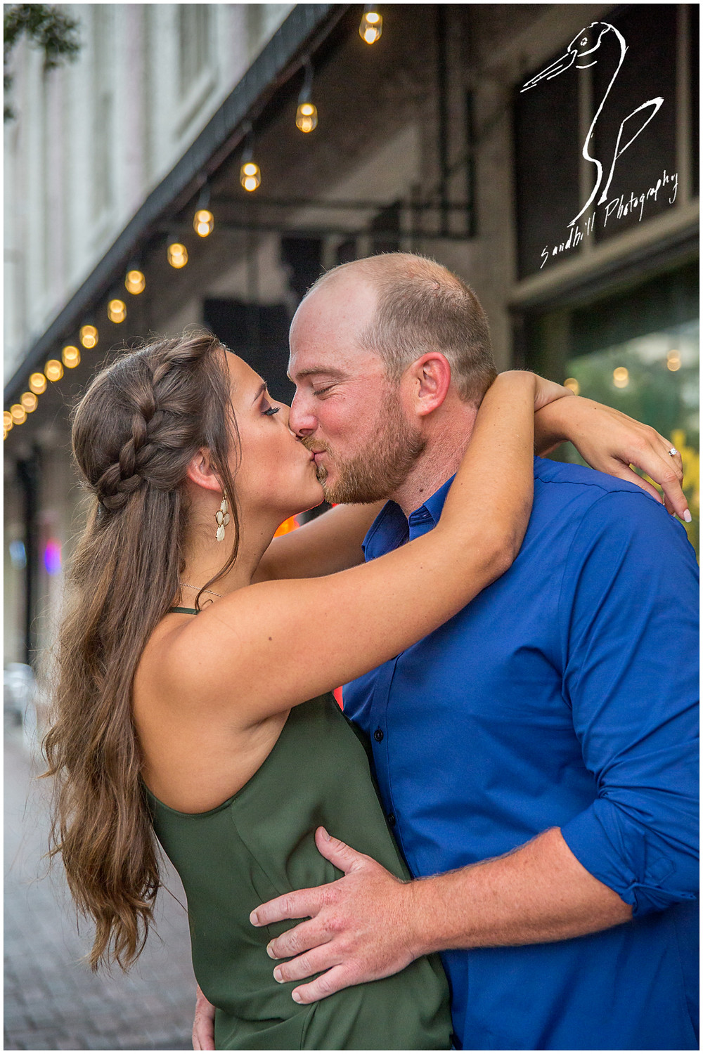 Downtown Bradenton Engagement Photography, a newly engaged couple share a kiss with the lights of an urban setting behind them