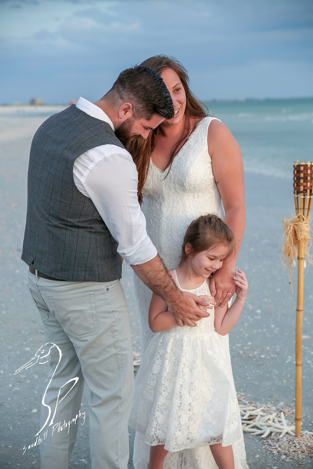 Treasure Island Wedding, ceremony on the beach, bride and groom are holding their daughter's hands