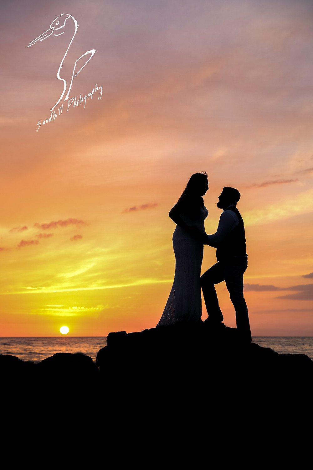 Treasure Island Wedding, Bride and Groom silhouetted against the sunset on the rocks