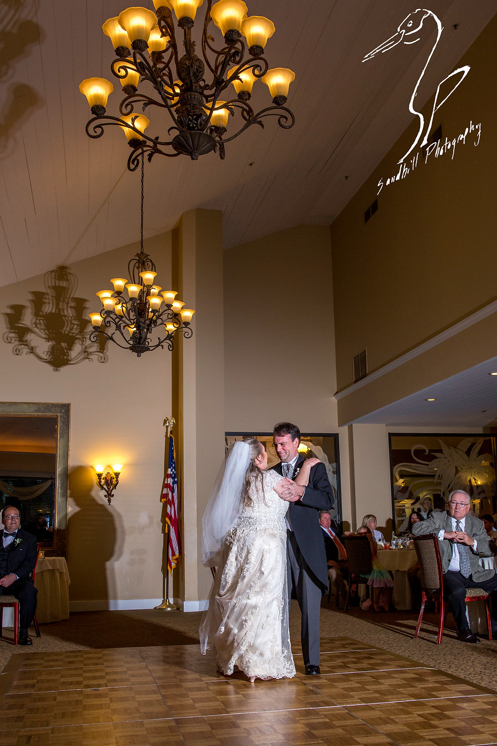 Rainy Day Wedding Photography Sarasota, First dance with bride and groom on the dance floor under chandeliers