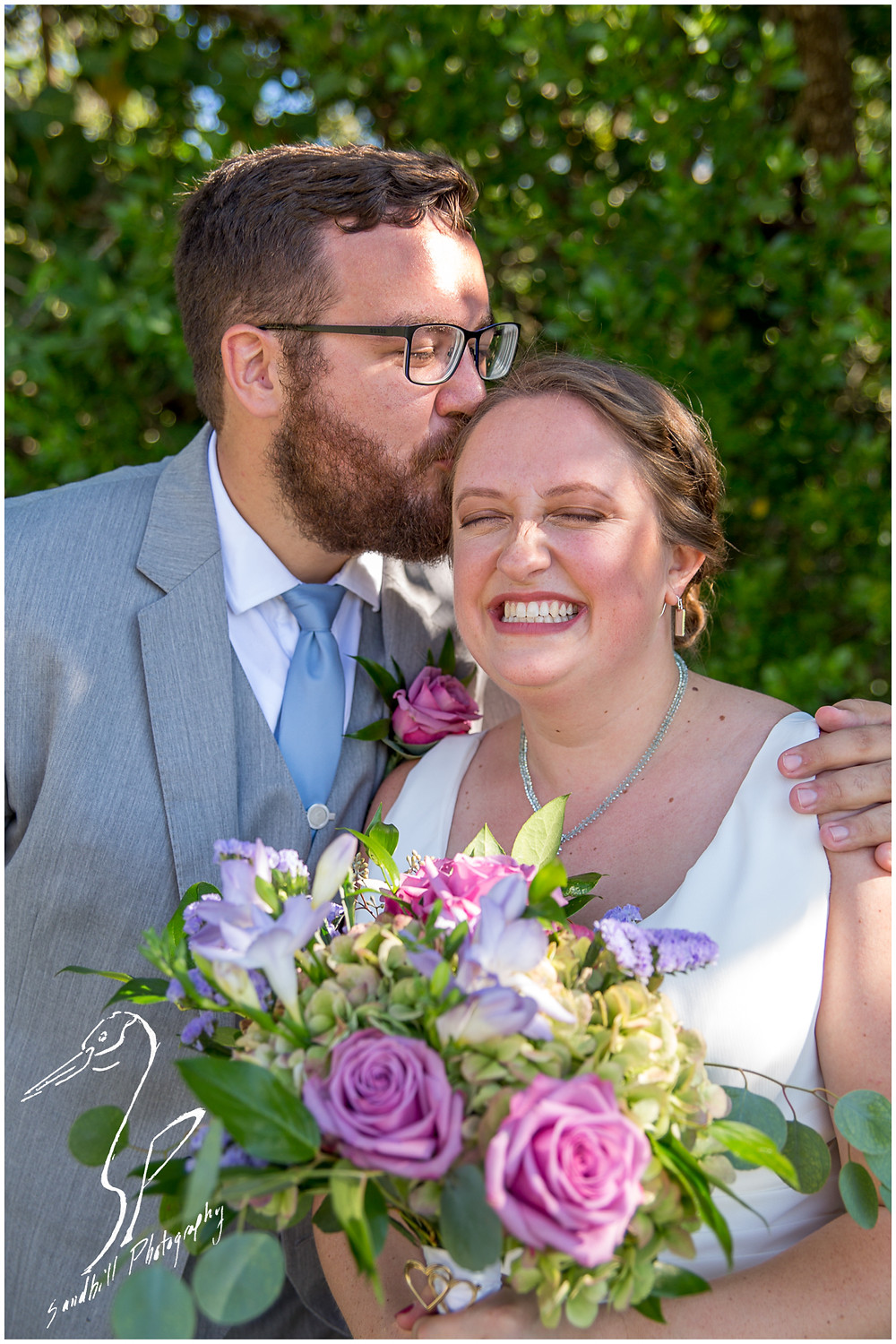 Van Wezel Wedding Photography, portrait a groom kissing his bride as she smiles in Sarasota