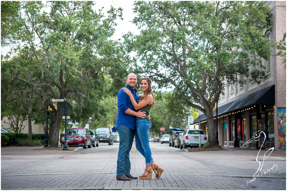 Downtown Bradenton Engagement Photography an engaged couple standing in the middle of the road on Main Street