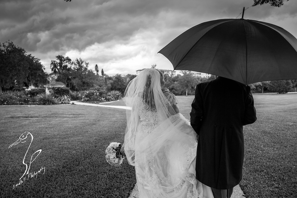 Rainy Day Wedding Photography Sarasota, Bride and groom walking under an umbrella in Phillipi Estate Park, black and white