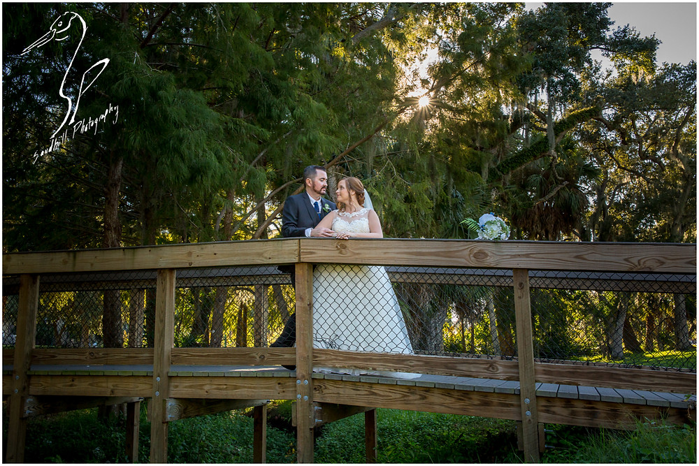 Sarasota Wedding Photography Crocker Memorial Church bride and broom stand on a bridge with the sun behind them
