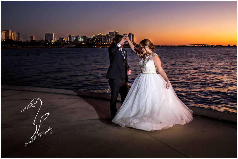 Sarasota Wedding Photography sunset pictures of bride and groom on Sarasota Bay with city skyline in background by Sandhill Photography