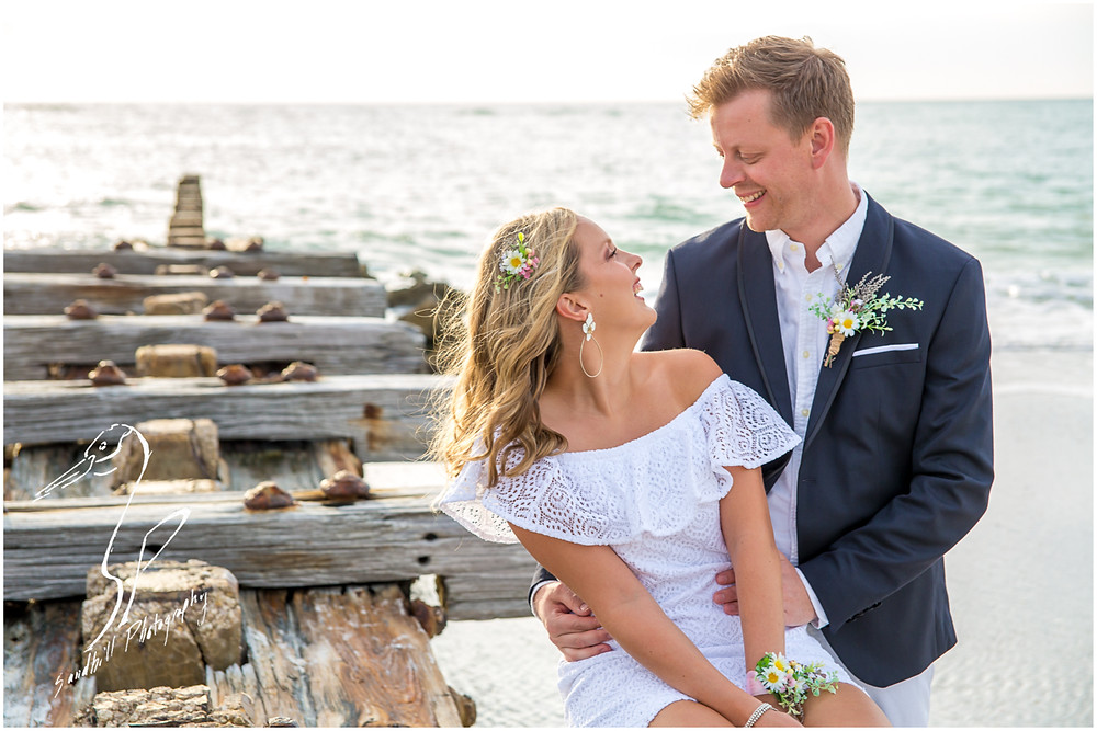 Anna Maria Island Wedding Photography, couple sits on the Coquina Beach jetty, by Sandhill Photography