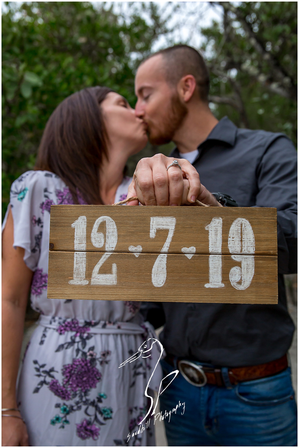 Bradenton Engagement Photographer, couple kiss behind their rustic save the date sign, by Sandhill Photography.
