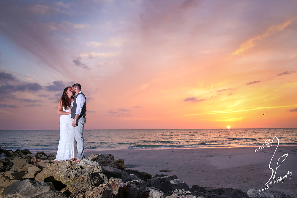 Treasure Island Wedding, Bride and Groom embracing with a kiss on the rocks at sunset