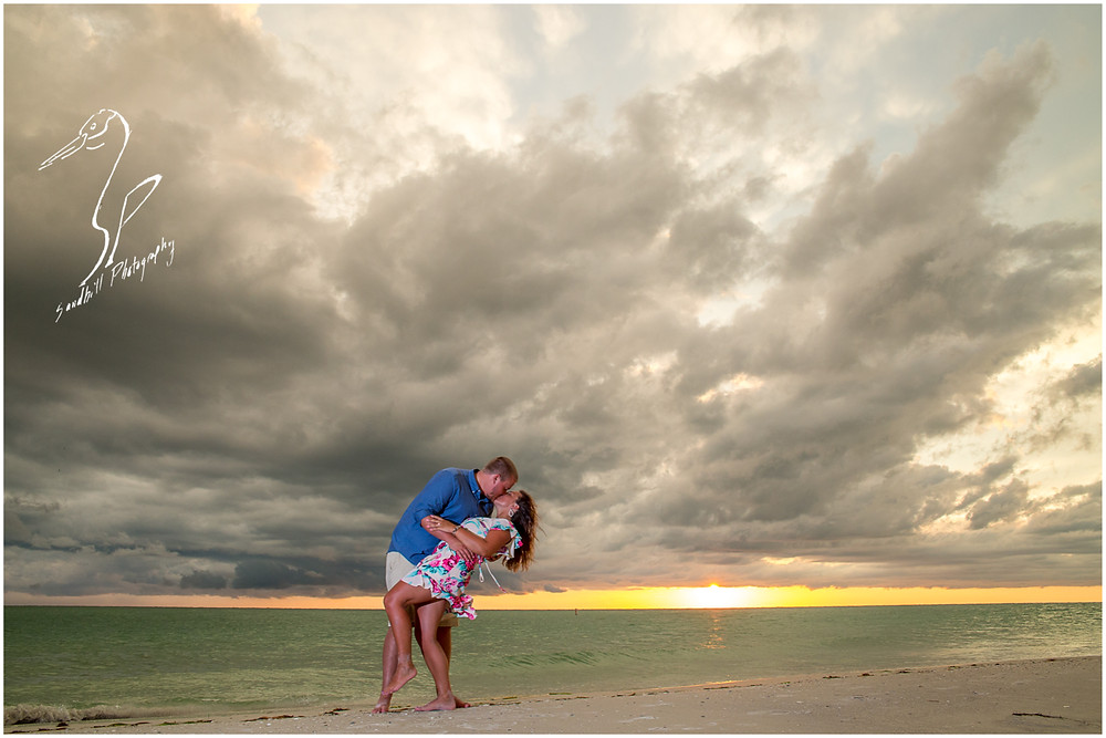 Bradenton Beach Engagement Photography, a couple share a kiss at sunset with storm clouds in the background