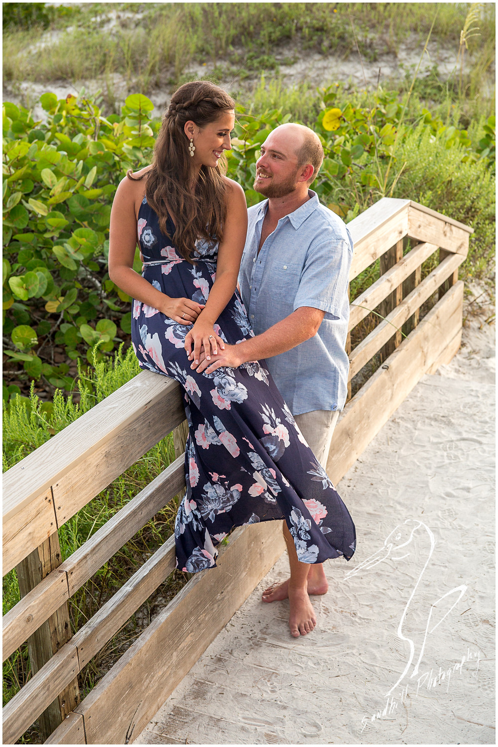 Beer Can Island Engagement Photography with engaged couple sitting on a beach boardwalk on Anna Maria Island looking at each other