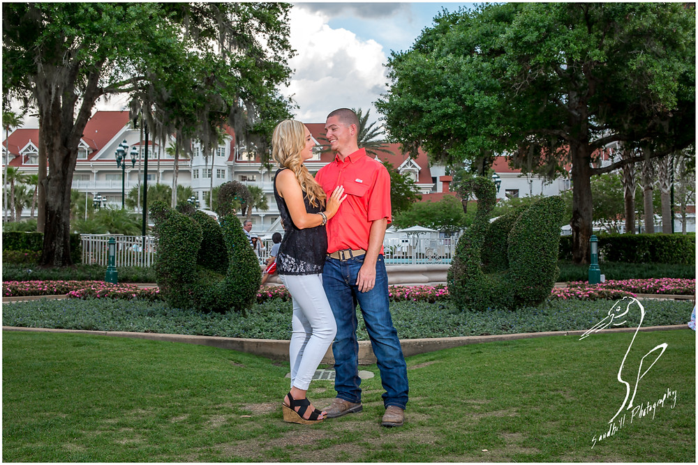 Disney's Grand Floridian Engagement Session, photography of engaged couple by sculpted swan bushes
