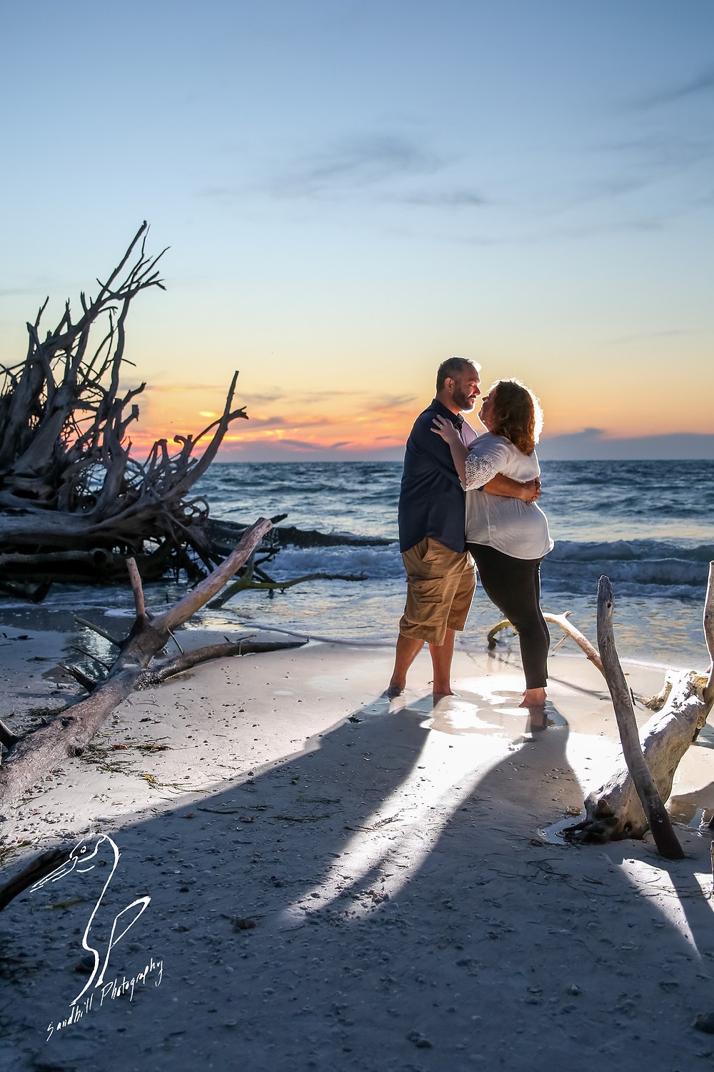 Beer Can Island Sunset Engagement Photography couple kiss drift wood dead trees sand beach ocean romantic flash backlit