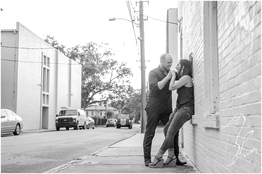 Downtown Bradenton Engagement Photography, in black and white, an engaged couple lean against a brick wall and laugh together.