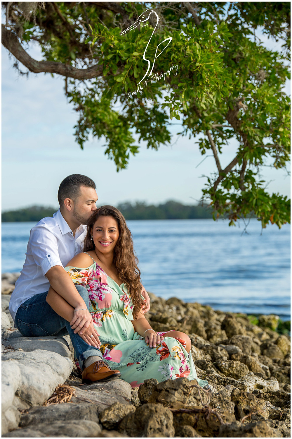 DeSoto National Memorial Photography, an engaged couple sit romantically on the rocks under a tree and the man kisses his fiance's head.