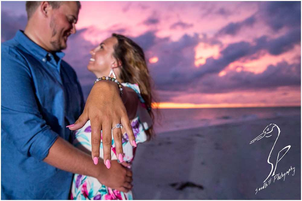 Bradenton Beach Engagement Photography, a newly engaged woman shows off her ring as her fiance holds her close.