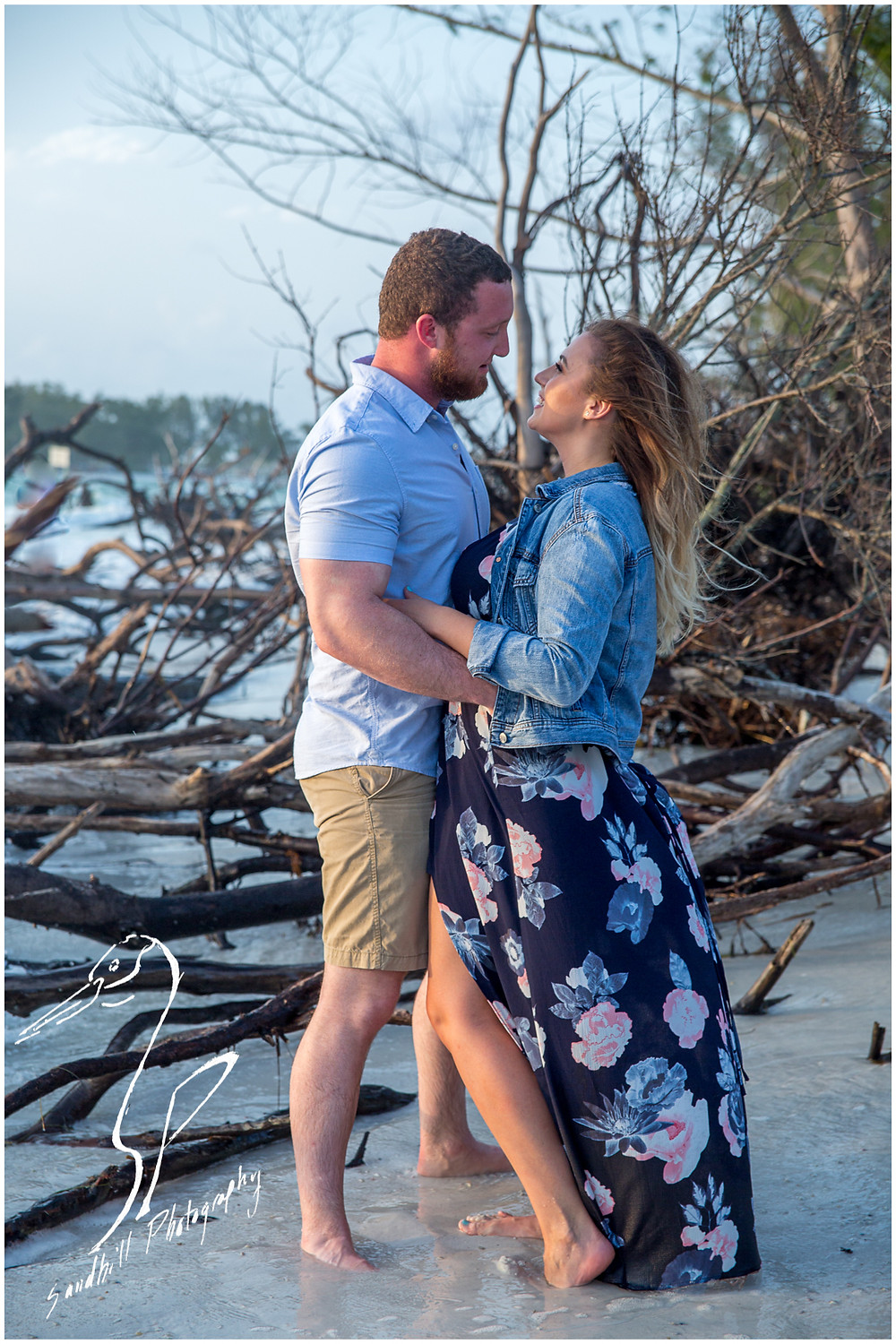Longboat Key Engagement Photographer, engaged couple embracing on a drift wood strewn beach