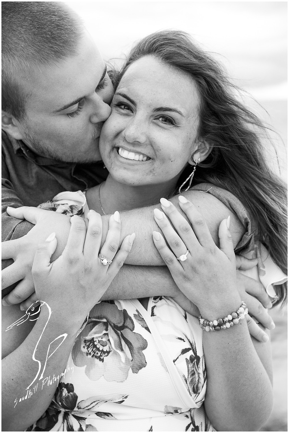 Bradenton Beach Engagement Photography, a man wraps his arms around his fiance's shoulders and kisses her while she smiles at the camera, black and white image by Sandhill Photography