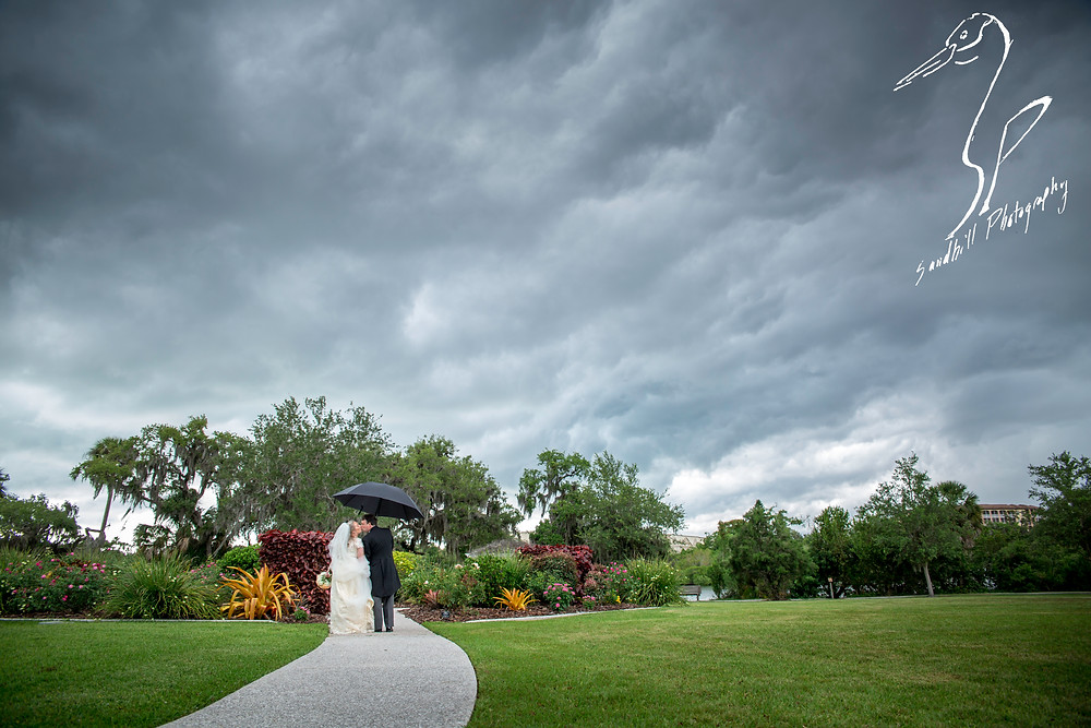 Rainy Day Wedding Photography Sarasota, Bride and Groom kissing under an umbrella at Phillipi Estate Park, Sandhill Photography