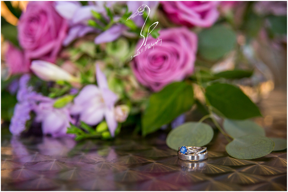 Van Wezel Wedding Photography, detail picture of wedding bands and engagement rings with bouquet in the background