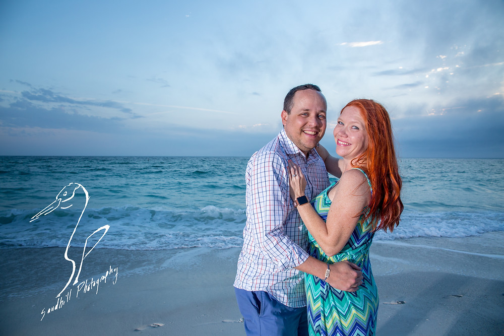 Anna Maria Island Engagement Session Holmes Beach Sunset flash Photography Engagement sand beach sky clouds couple smiles hand on chest hug