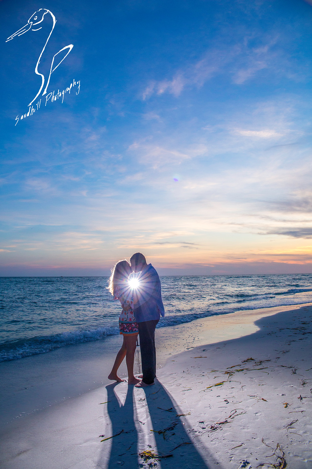 Longboat Key Surprise Proposal, engaged couple kissing at the beach at sunset in a backlit photograph
