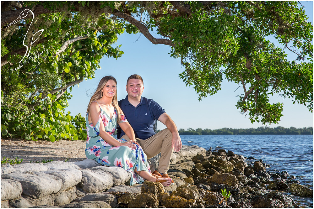 DeSoto National Memorial Photography, an engaged couple sit on the rocks at the shore of the Manatee River.