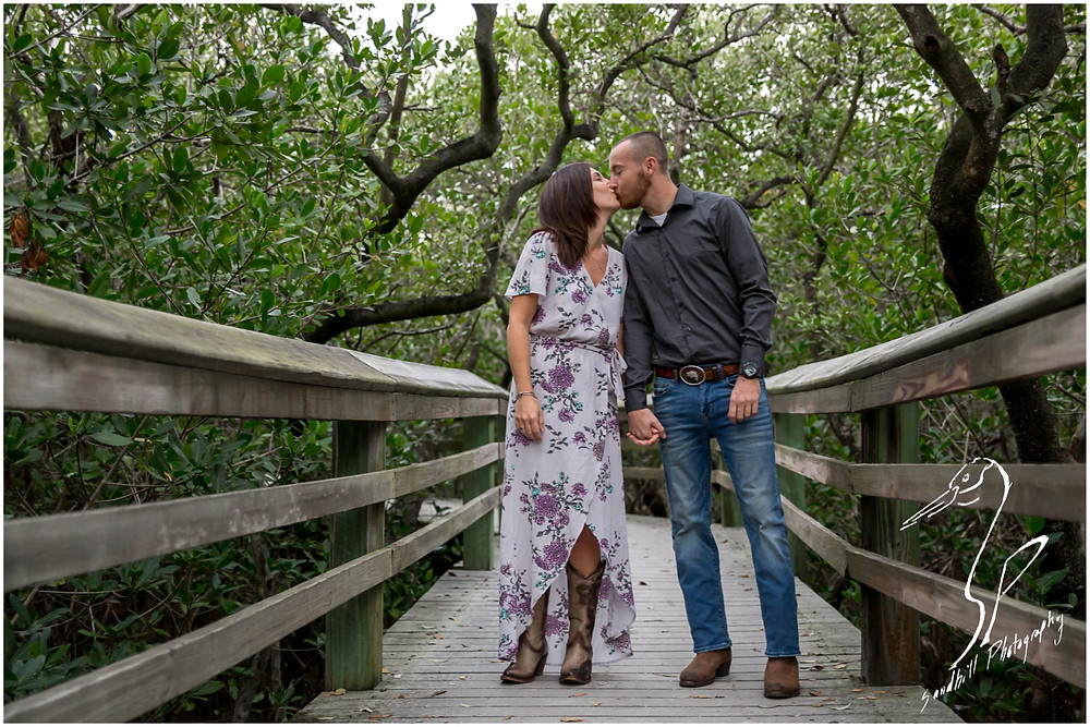 Bradenton Engagement Photographer, portrait of engaged couple kissing on a board walk through the mangroves, by Sandhill Photography