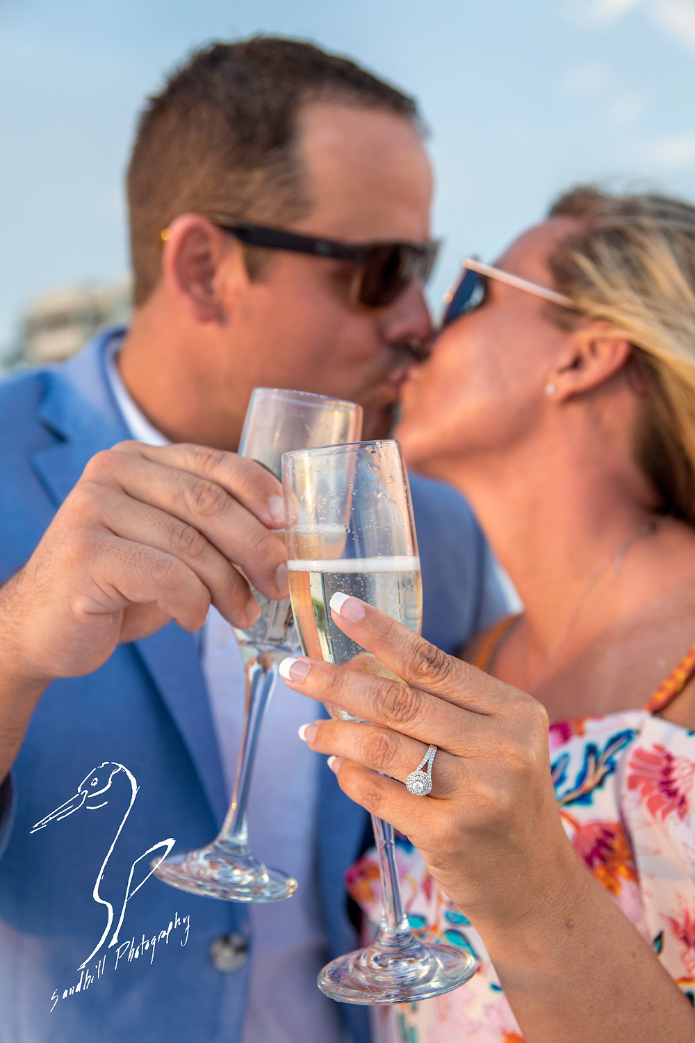 Longboat Key Surprise Proposal by Sandhill Photography with couple kissing behind champagne glasses with the engagement ring in focus