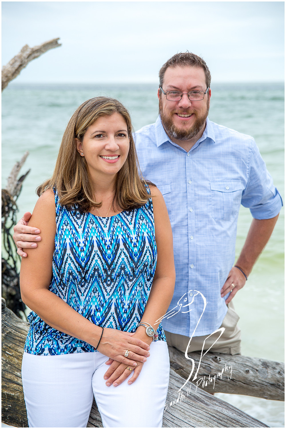 Longboat Key Family Photographer, husband and wife pose next to a drift wood tree on the beach at Beer Can Island