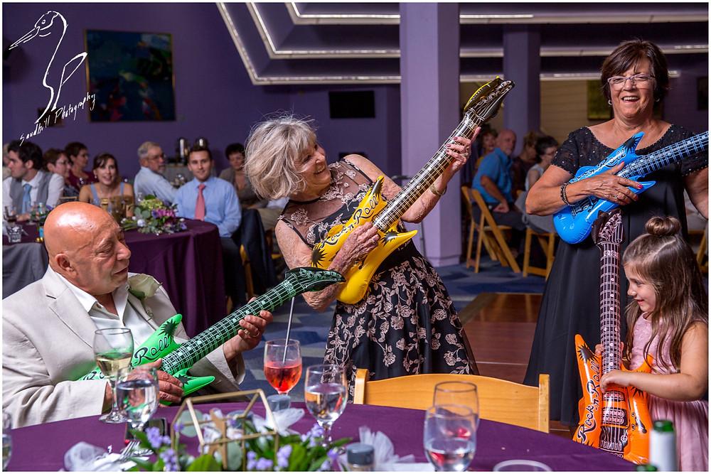 Van Wezel Wedding Photography, Grandparents play inflatable guitars at the reception, Sandhill Photogaraphy