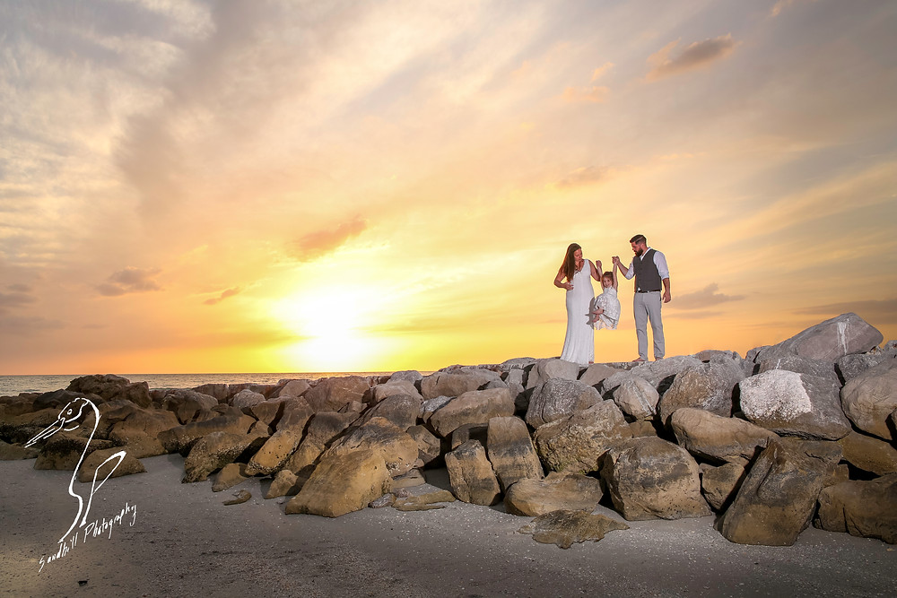 Treasure Island Wedding, Bride and Groom swinging flower girl on the rocks at sunset