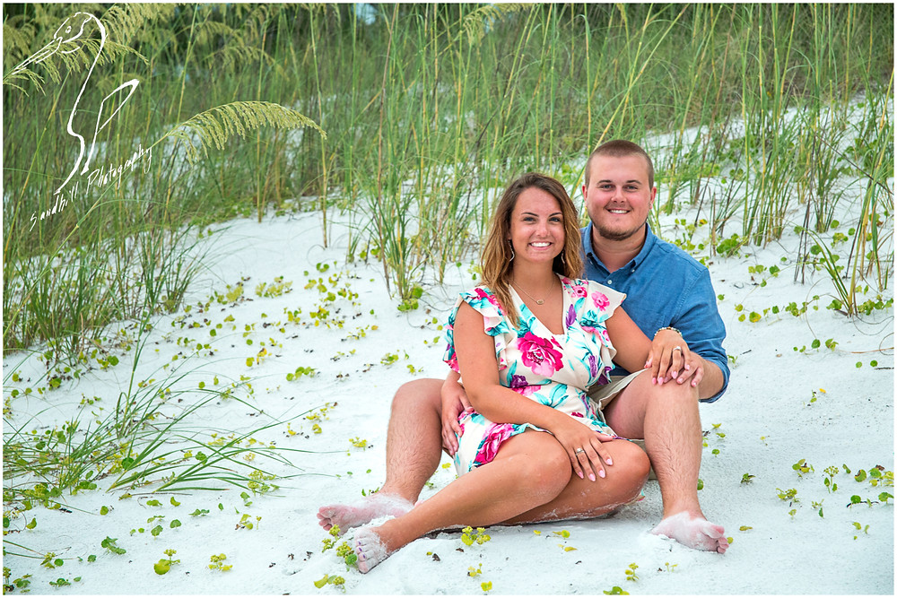 Bradenton Beach Engagement Photography, a couple sit in the dunes and smile towards the camera