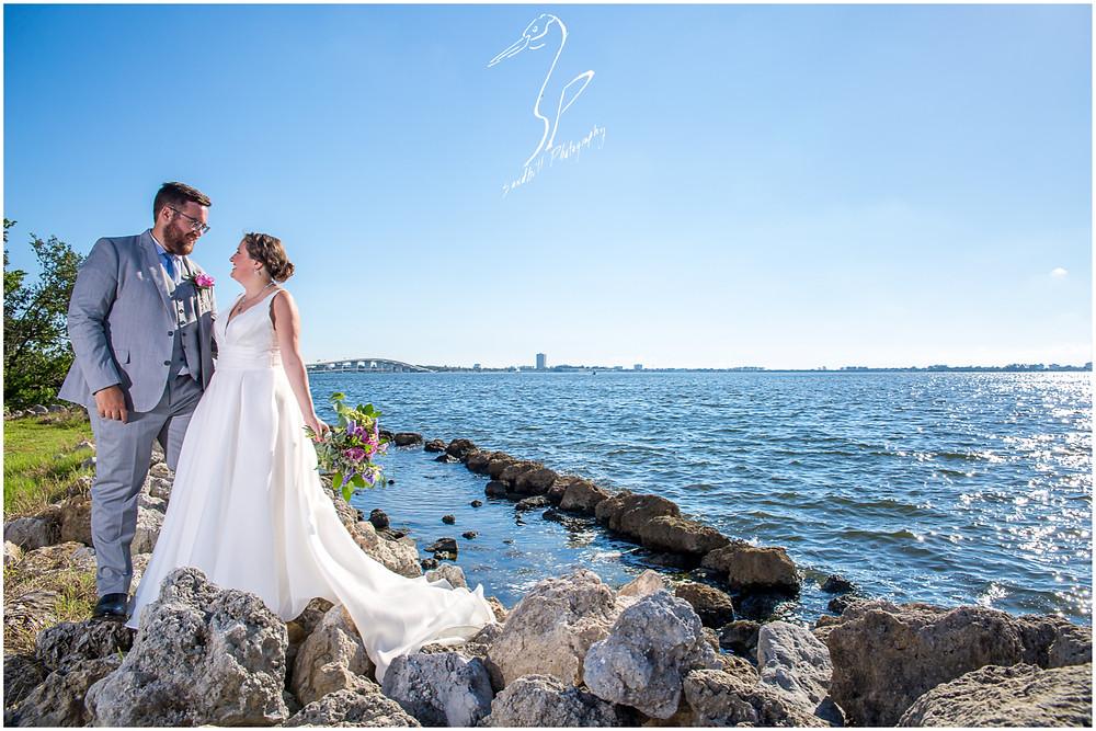 Van Wezel Wedding Photography, Dramatic portrait of bride and groom standing on the rocks beside Sarasota bay