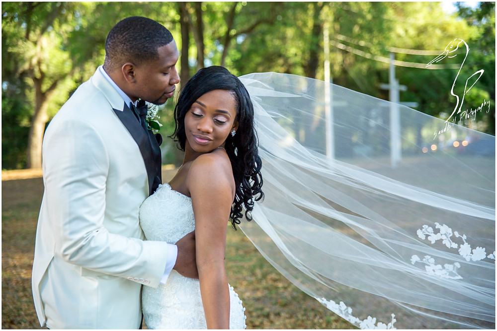 Bradenton Wedding Photographer, bridal portrait of Bride and Groom embracing with her veil in the wind, United Methodist Church of Seffner