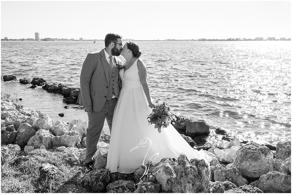 Van Wezel Wedding Photography, Black and White bridal portrait of the bride and groom kissing on the rocks in front of Sarasota Bay