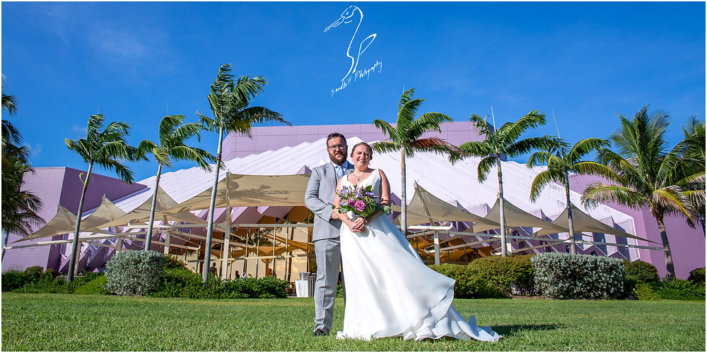Van Wezel Wedding Photography, a bride and groom pose outside of the Performing Arts Hall in Sarasota