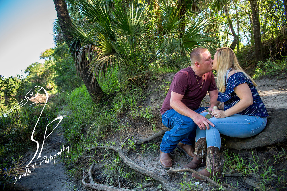 Rye Preserve Engagement Photography in Bradenton, couple sitting on the bank of the Manatee River and sharing a kiss.  Sandhill Photography