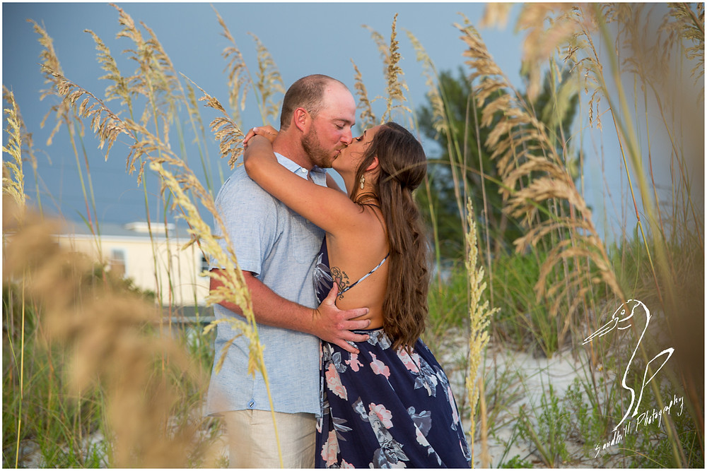 Beer Can Island Engagement Photography, couple embracing and kissing in the sand dunes at the beach