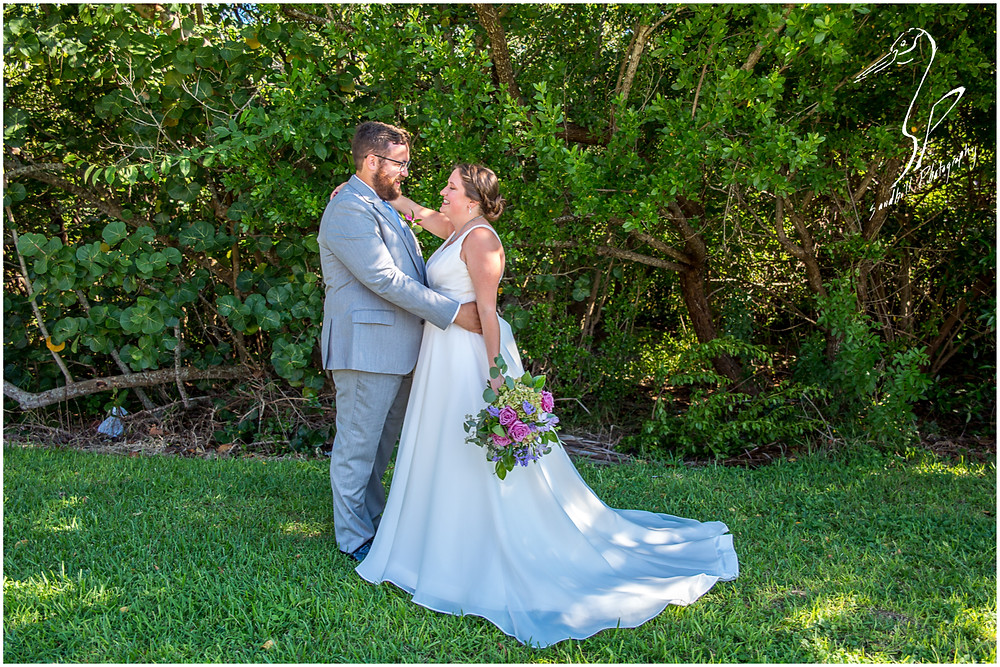 Van Wezel Wedding Photography, portrait of bride and groom standing in the grass at the edge of the woods in Sarasota