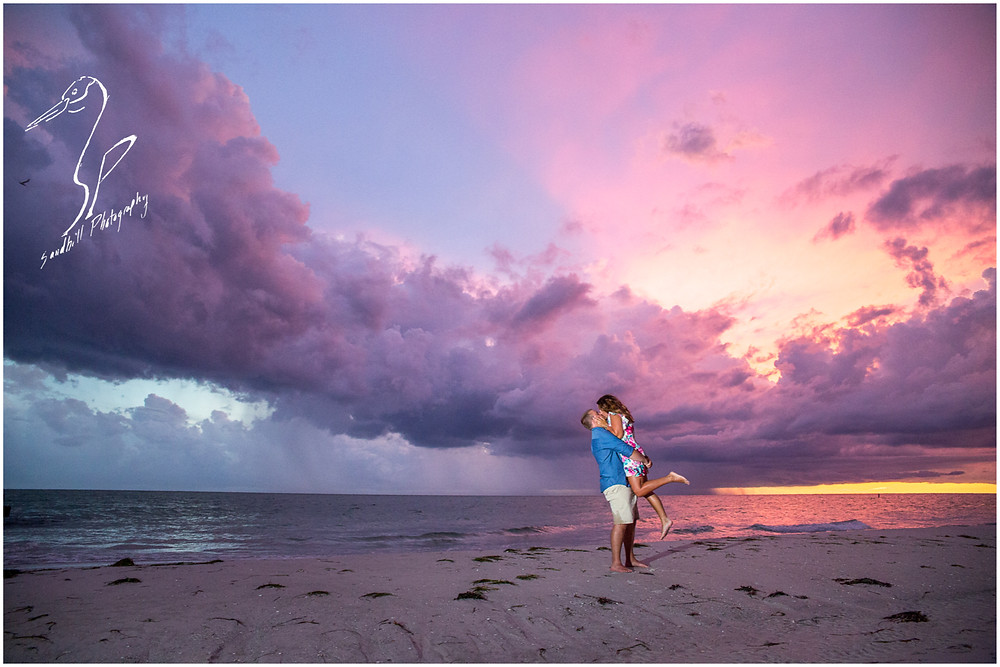 Bradenton Beach Engagement Photography, a man lifts his fiance in his arms during a sunset with purple clouds, by Sandhill Photography