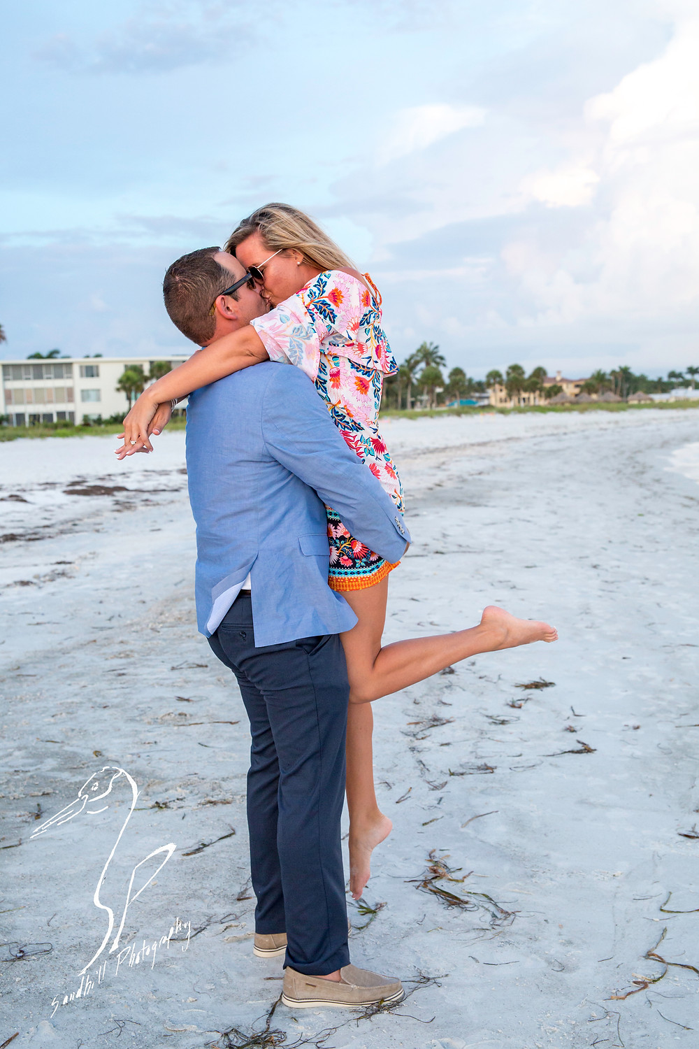 Longboat Key Surprise Proposal man picks up his fiance to kiss her on the beach