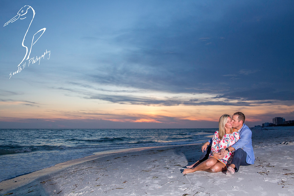 Longboat Key Surprise Proposal, engaged couple sitting in the sand embracing at sunset