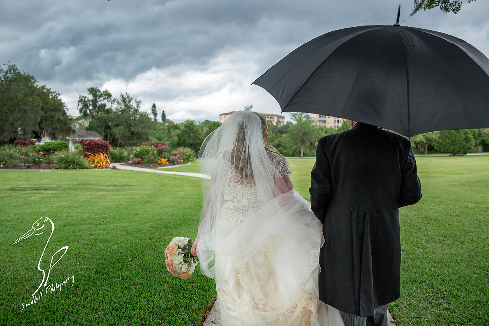 Rainy Day Wedding Photography Sarasota Bride and groom carrying umbrella in the park, Sandhill Photography