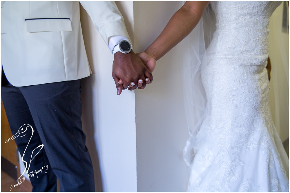 Bradenton Wedding Photographer, the bride and groom clasp hands as they share a first touch before their wedding, separated around a corner at United First Methodist Church of Seffner