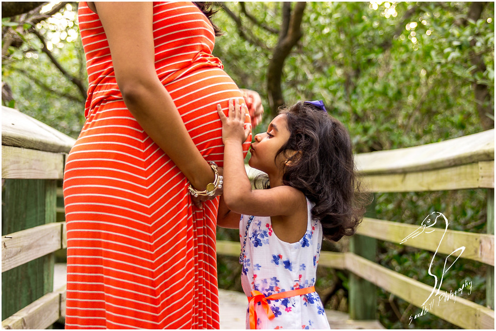 DeSoto National Memorial Photography, sweet Maternity photo shoot with a little girl kissing her mother's belly while standing on a boardwalk